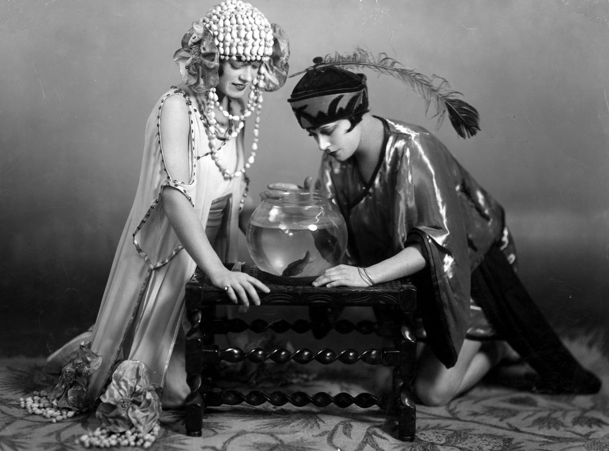 Circa 1925: Two actresses looking at fish in a bowl during a performance of Aladdin.
