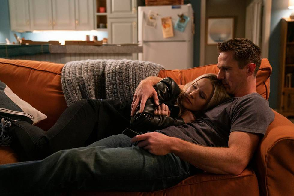 Kristen Bell as Veronica Mars and Jason Dohring as Logan cuddle on a couch.