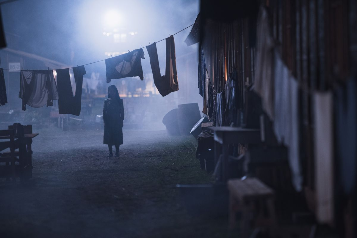 A young woman stands outside a shabby dwelling at night underneath a line of washing hung to dry.