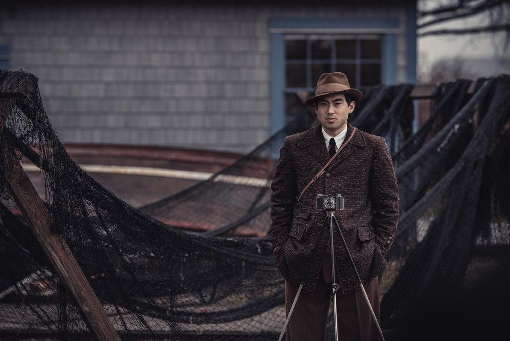 A young man in a 1940s-style suit and fedora stands behind a camera on a tripod and in front of fishing nets hung to dry.