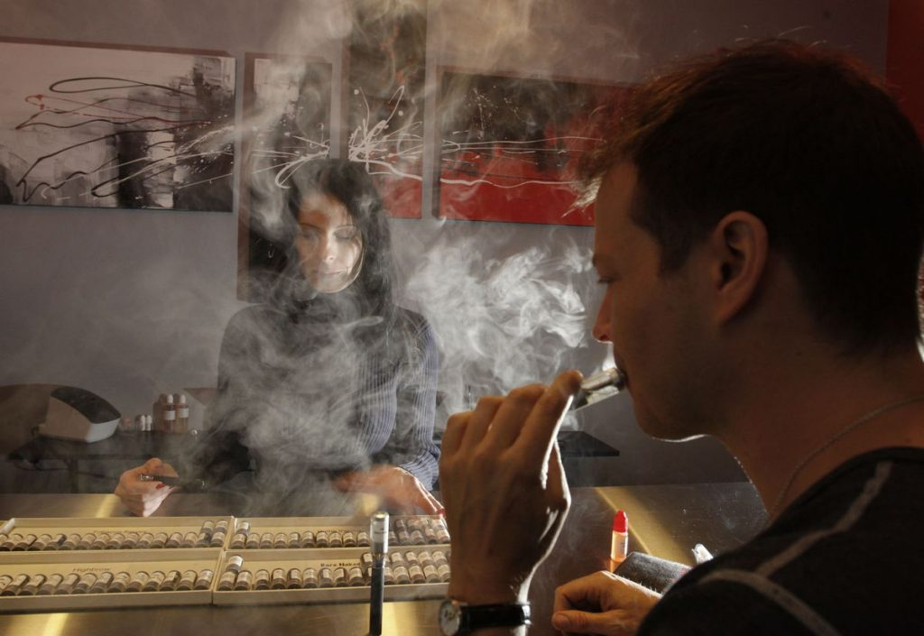 A man tests out vapes in a shop.
