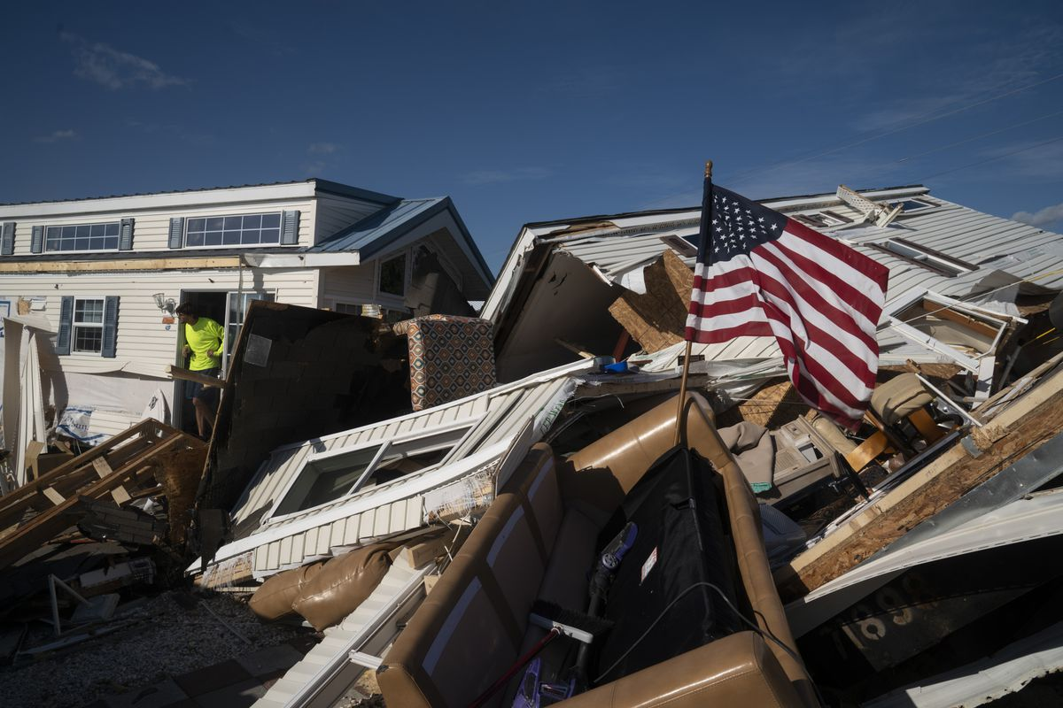 An American flag flies atop a stack of ruined homes and destroyed furniture.