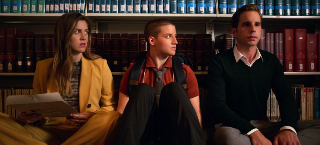 """Three members of the cast of """"The Politician"""" sit on the floor of a library."""