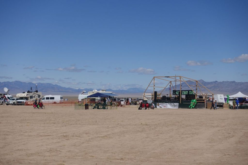 A few tents and vans by a stage being set up in a dirt field.