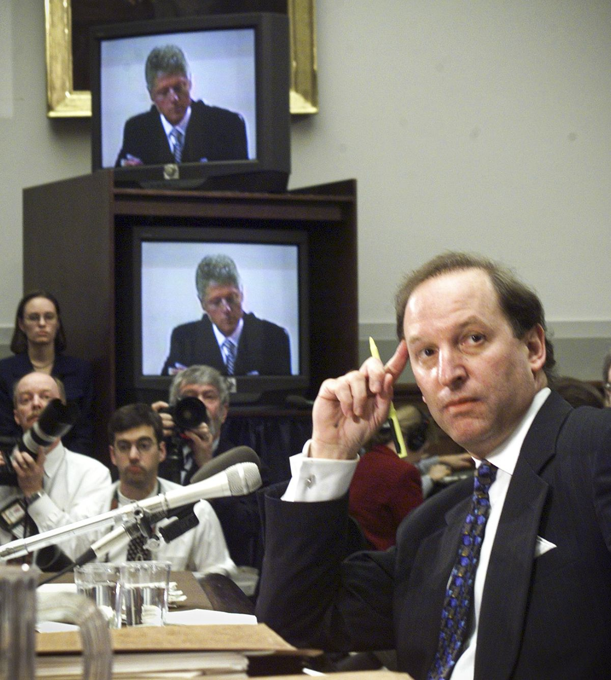 President Clinton's 1998 impeachment committee hearing with Clinton on a TV screen and Minority Chief Investigative Counsel Abbe Lowell watching him.