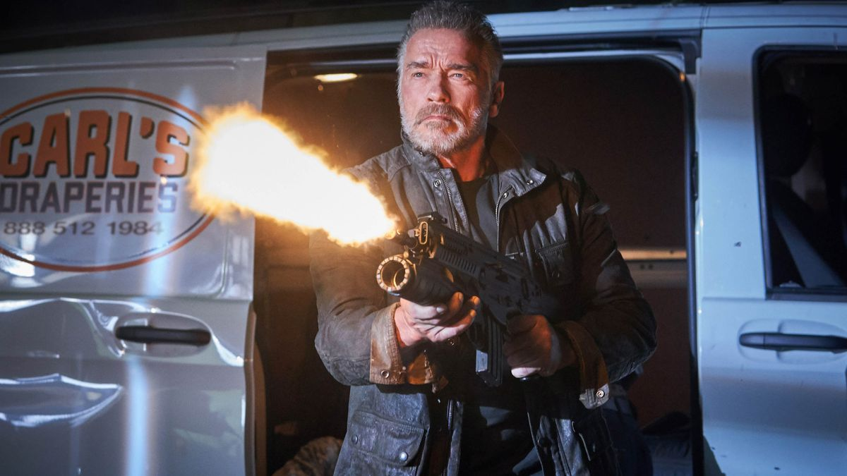 Arnold Schwarzenegger in Terminator: Dark Fate stands outside a van and shoots a flamethrower.