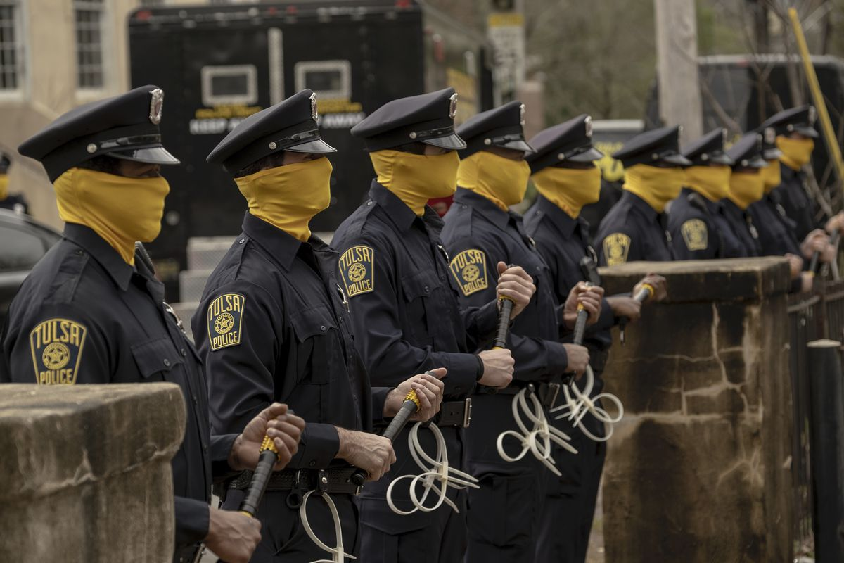 The police wear yellow masks to hide their faces.