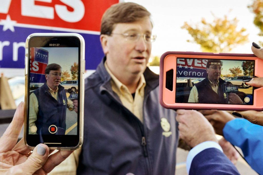 People hold up their phones to take photos and video of Tate Reeves.