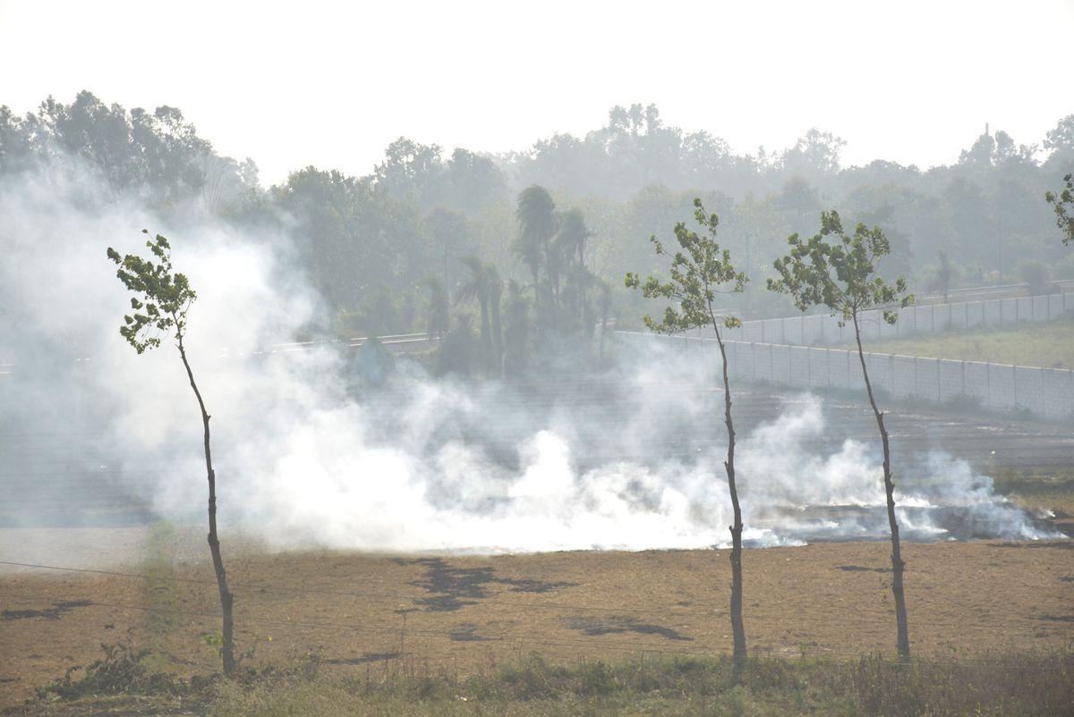 A fire to rid of crop stubble raises smoke at a farm near Masuri on November 4, 2019 in Ghaziabad, India.
