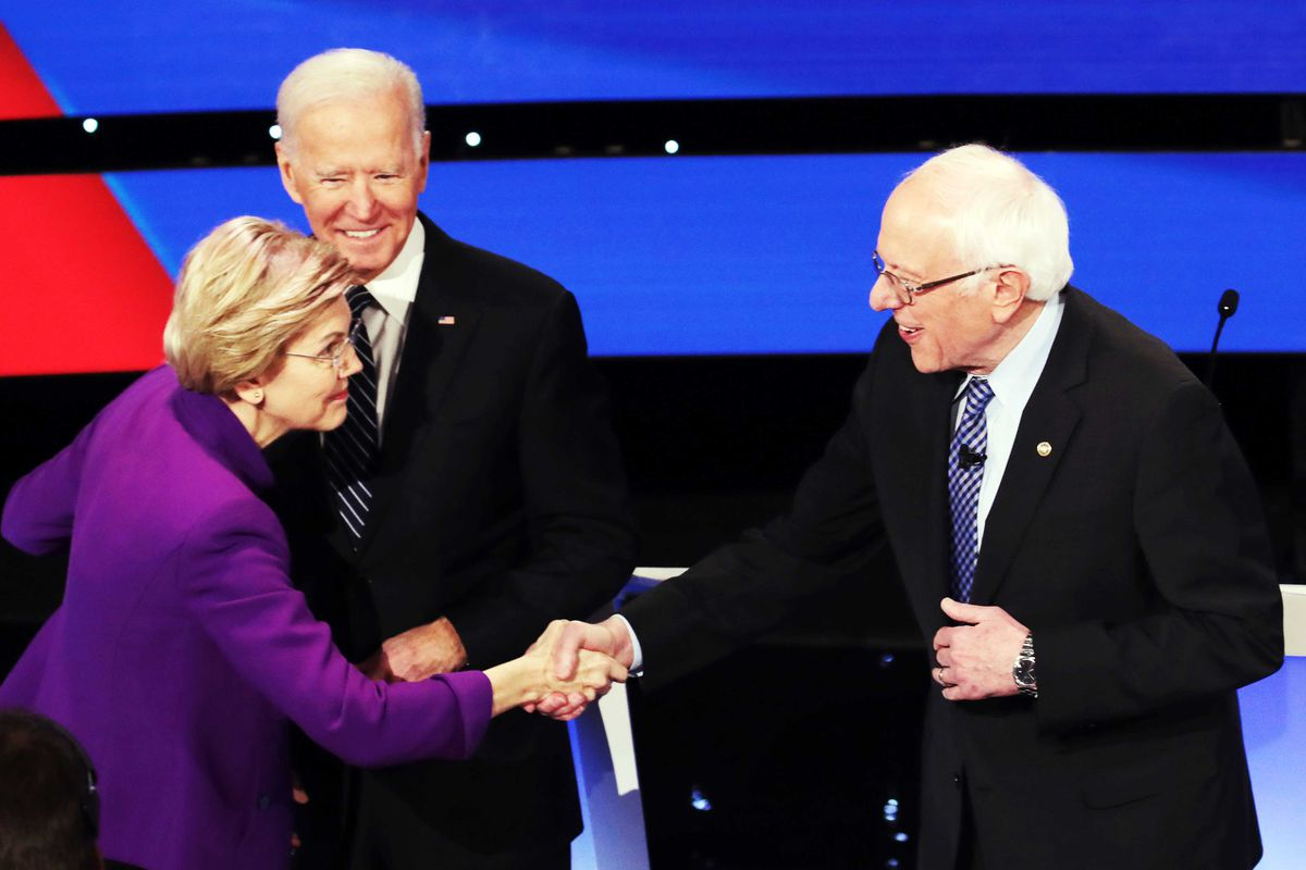 Elizabeth Warren shakes Bernie Sanders' hand while Joe Biden looks on.