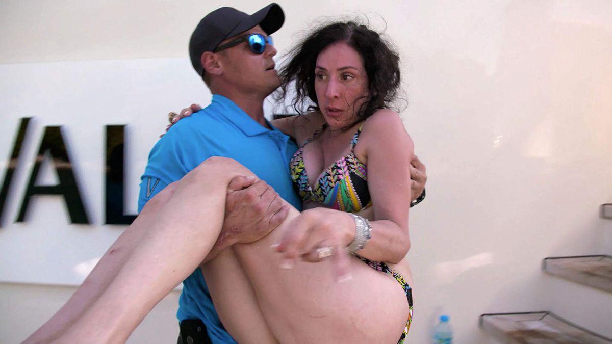 A man carries a bikini-clad woman across the deck of a yacht.