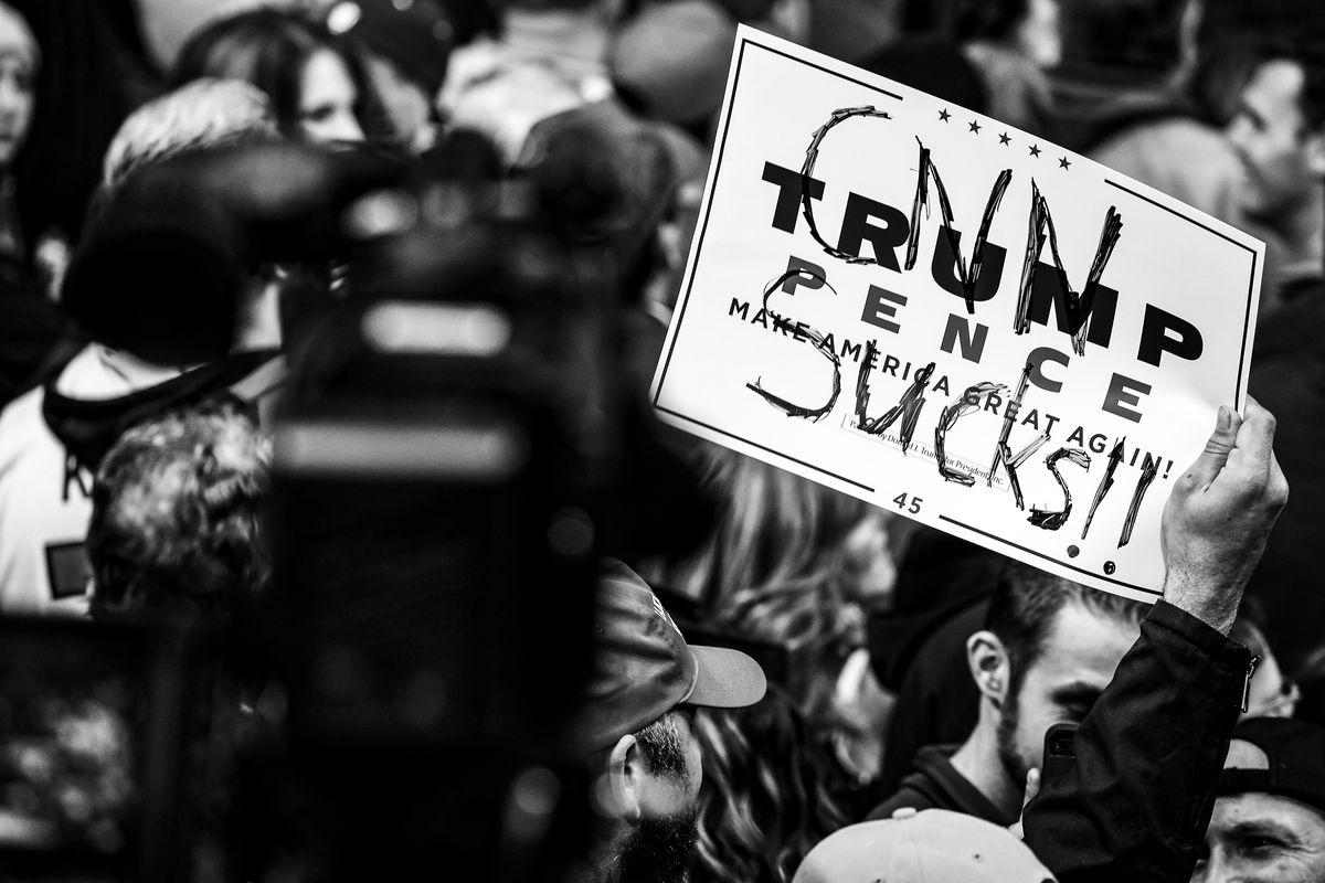 "A man holding a sign with ""CNN sucks"" scrawled over a Trump-Pence logo."