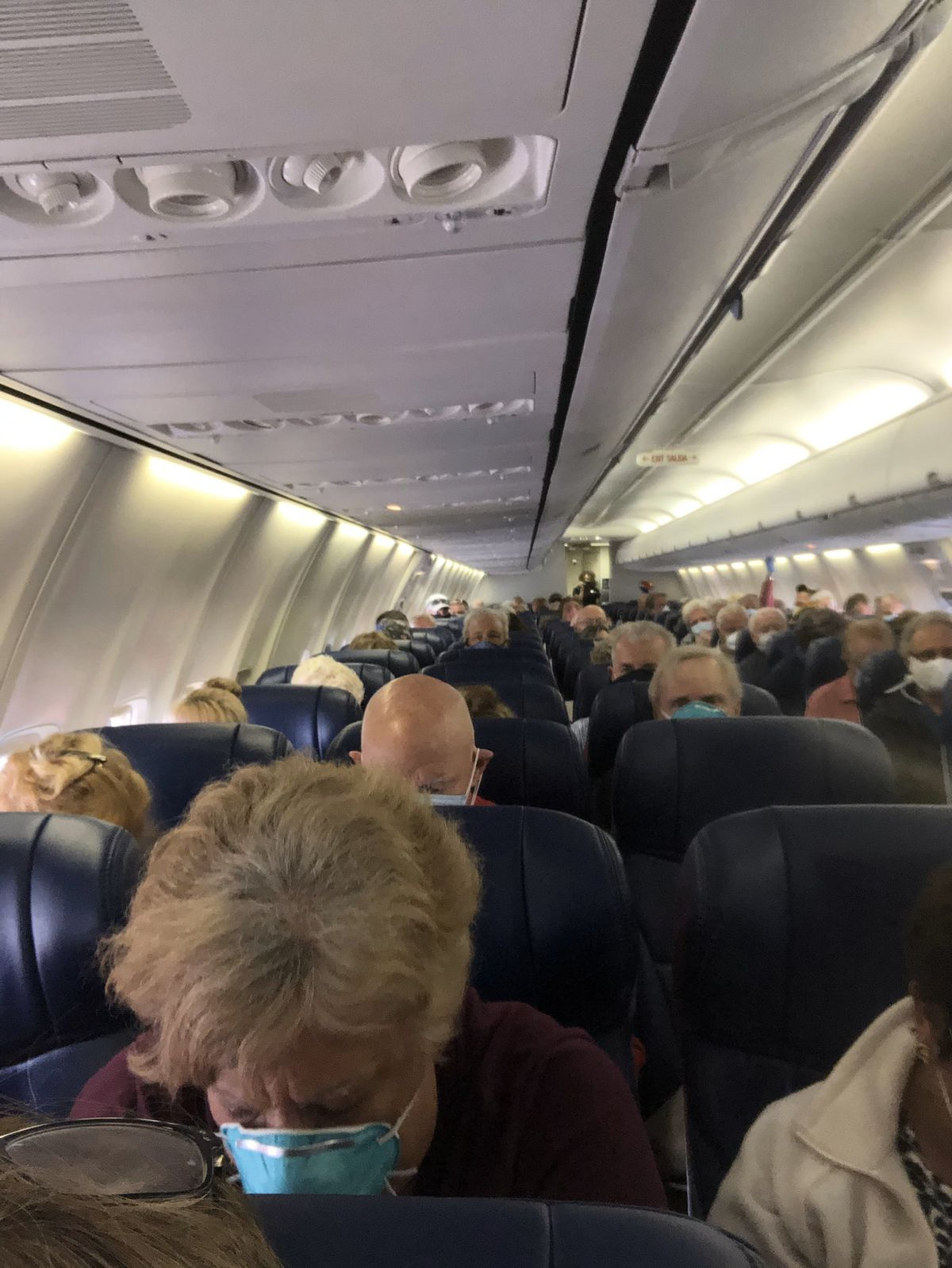 A crowded plane with elderly masked people.