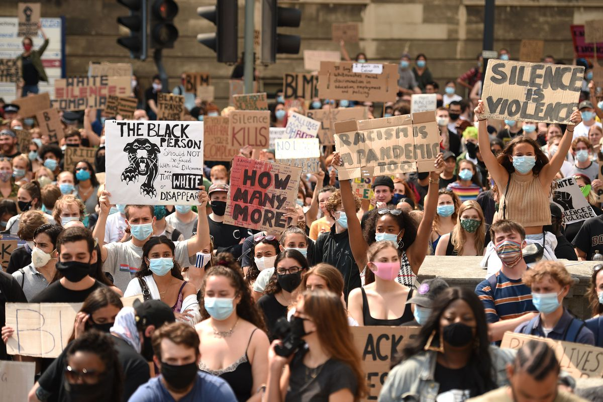 """Hundreds of people are packed together in a street. In masks, they hold up signs with messages like """"How Many More?"""" and """"Racism is a pandemic too."""""""