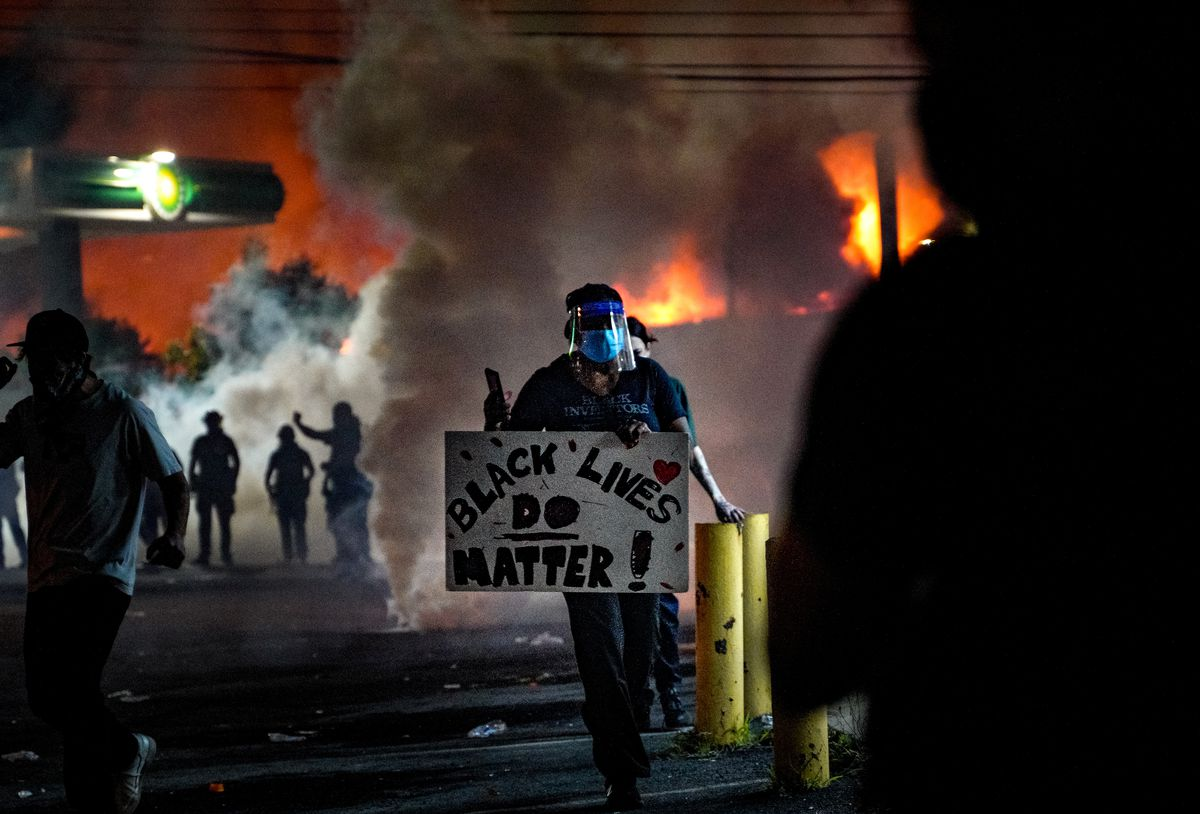 """Amid smoke from the fire and from what appear to be canisters, protesters stand in small groups. One, alone, walks towards the camera, with a sign reading """"Black Lives Do Matter!"""""""