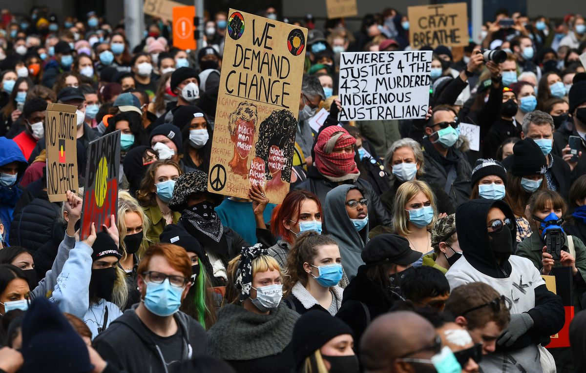 """A mass of diverse people stand masked and shoulder to shoulder. Many hold signs; one reads """"Where's the justice 4 the 432 murdered indigenous Australians?"""""""