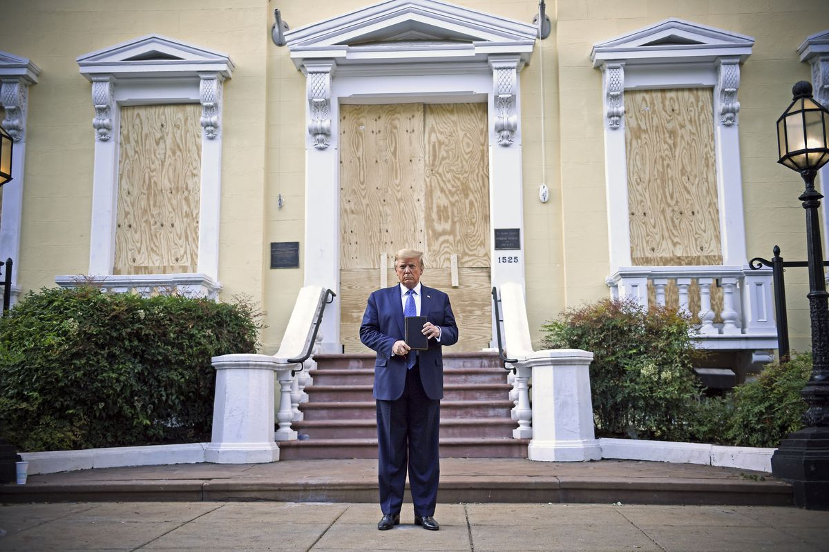 Trump, in a navy suit and blue tie, holds the top and bottom of a bible, frowning slightly in front of St. John's iconic yellow exterior, now boarded up.