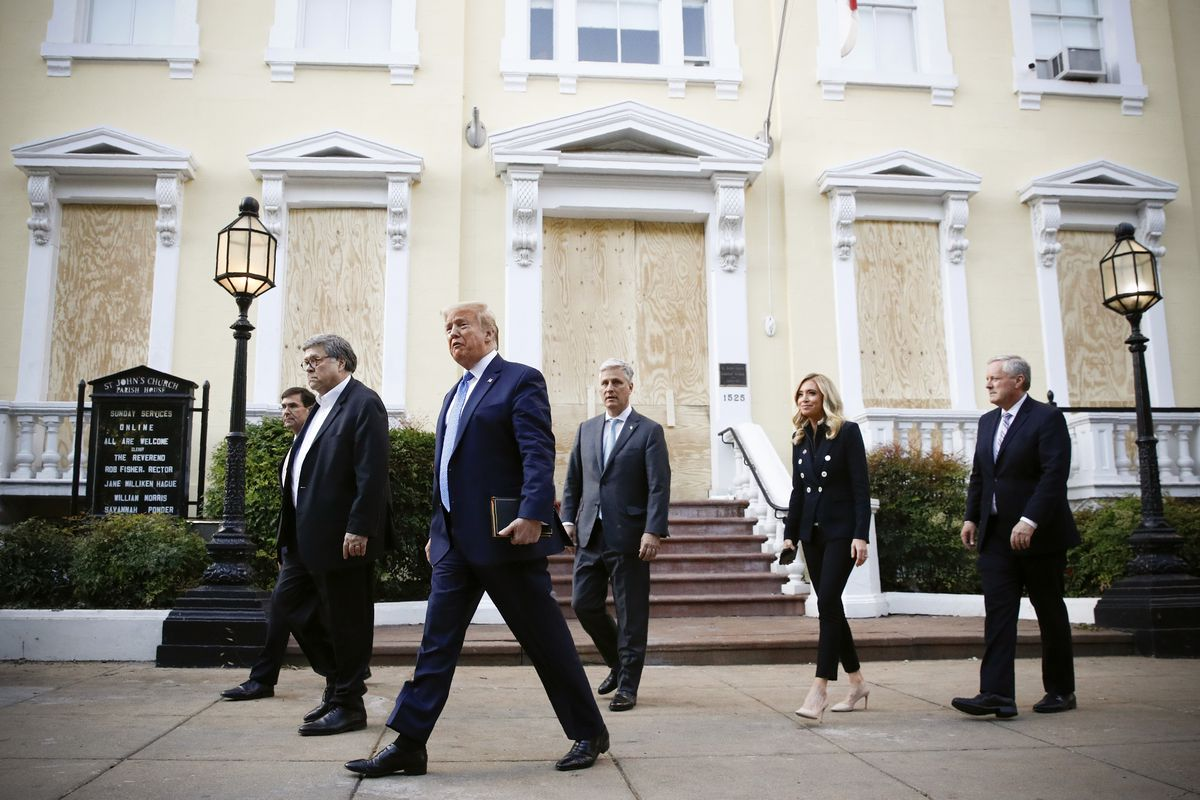 Trump, flanked by the officials noted above — all in dark suits, all sober, except for McEnany, who is smiling slightly, walks away from the boarded up St. John's.