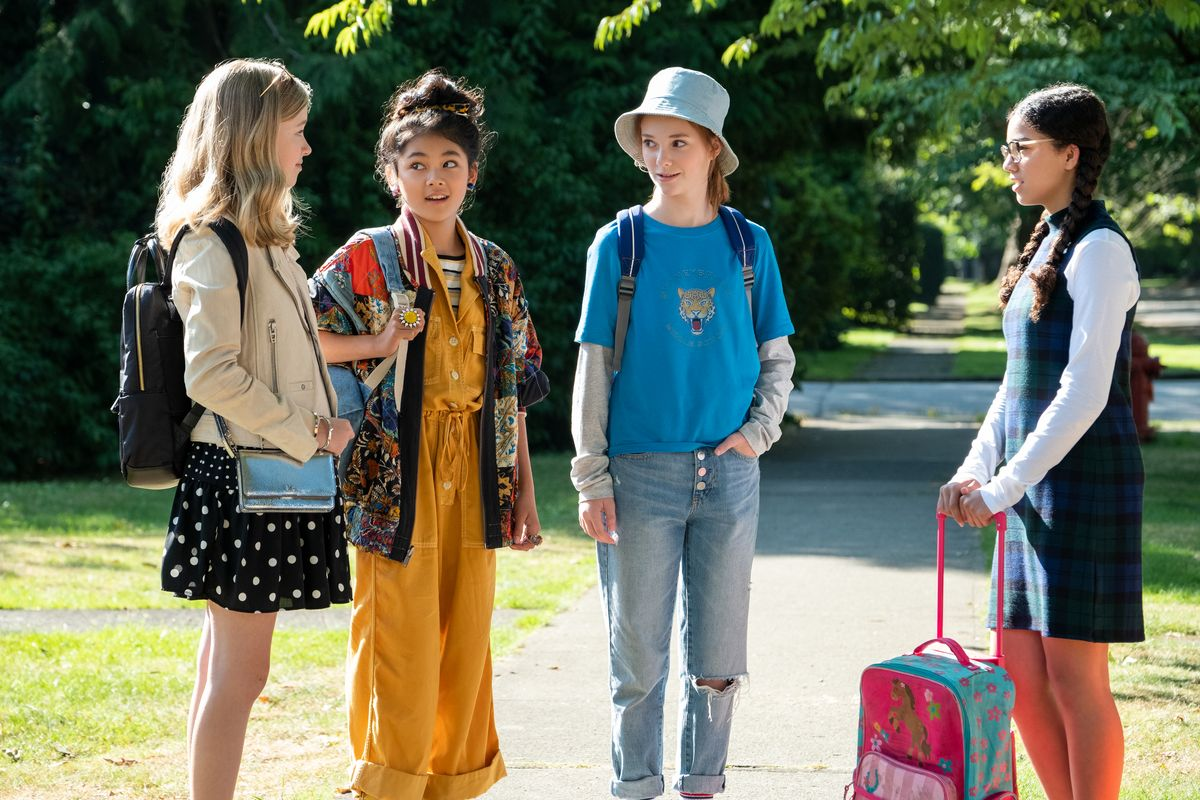 Four 12-year-old girls stand outside on a suburban street, carrying bookbags. Claudia is in a yellow jumpsuit, striped shirt, and patchwork jacket.
