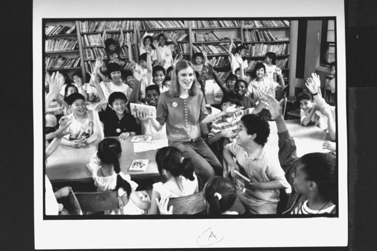 A white woman sits in a classroom, surrounded by young Asian American children holding books and watching her adoringly.