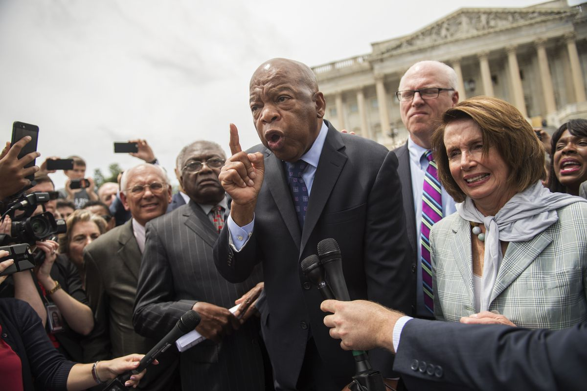 Lewis appears angry, his face strained as he speaks surrounded by Democratic leaders, including Nancy Pelosi and James Clyburn.