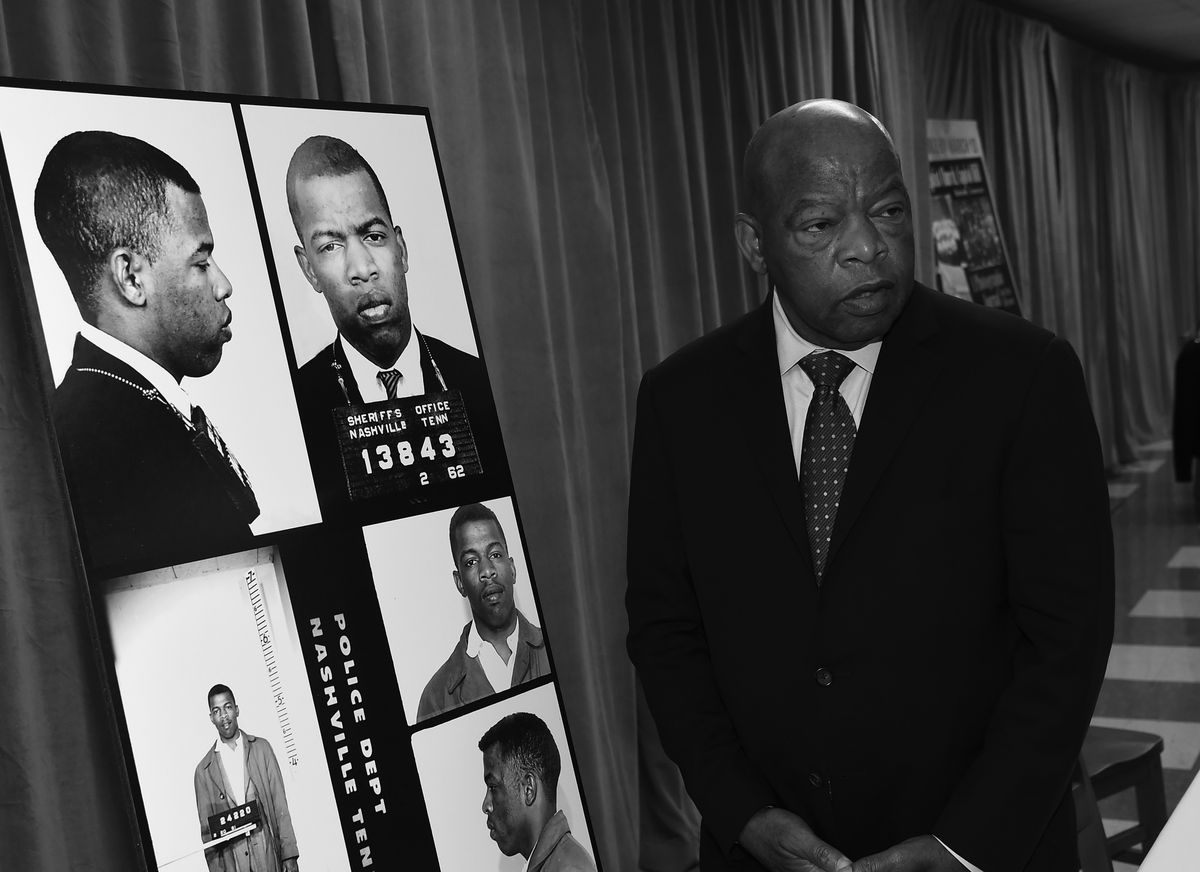 In a black and white photo, Lewis, in a dark suit, looks at five images of his younger self — all mug shots — taken following various arrests.