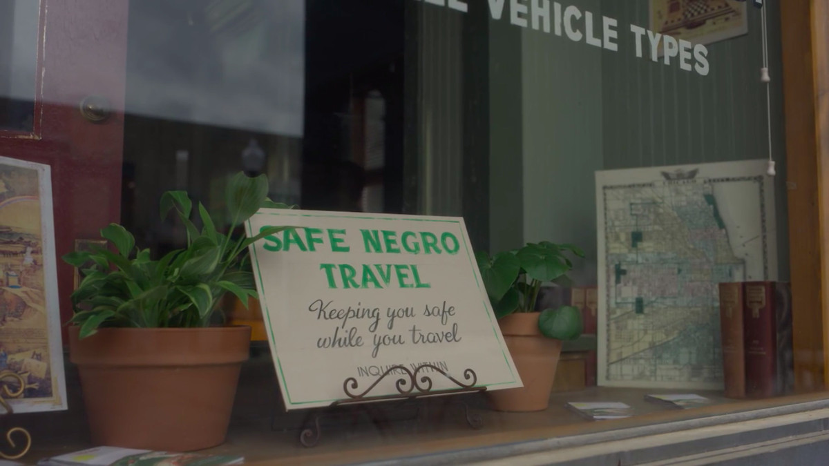 """A sign on display in a shop window reads, """"Safe Negro Travel. Keeping you safe while you travel. Inquire within."""""""