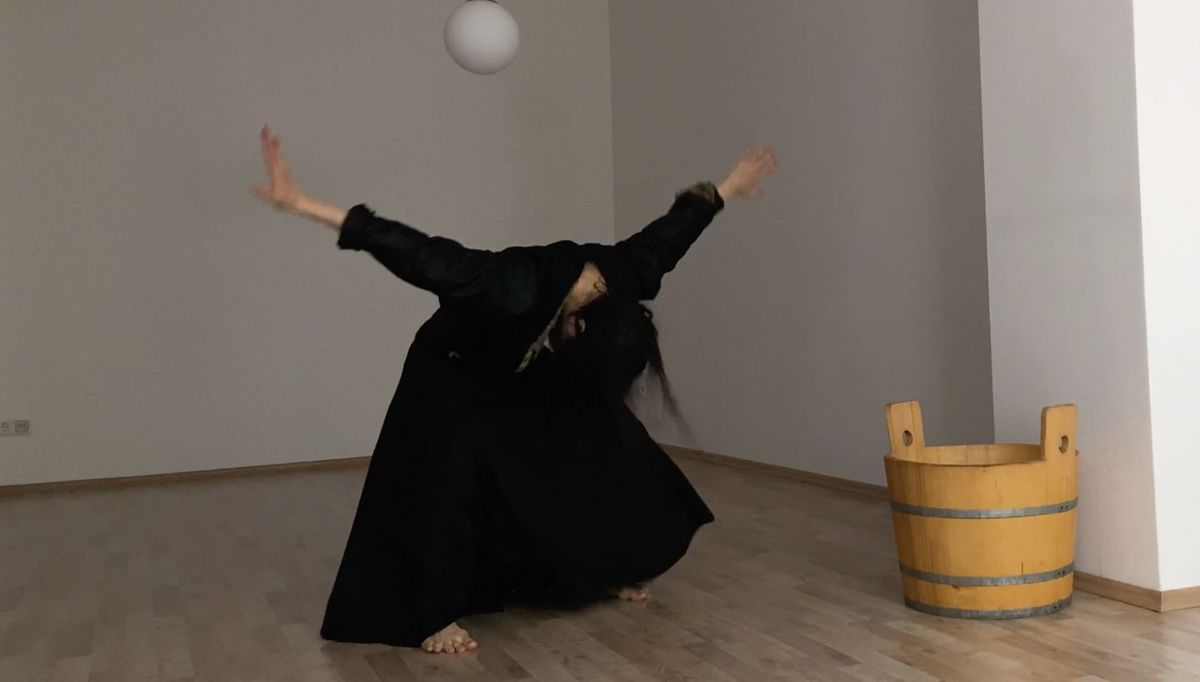 A dancer bows alone in a room, next to a wooden bucket.