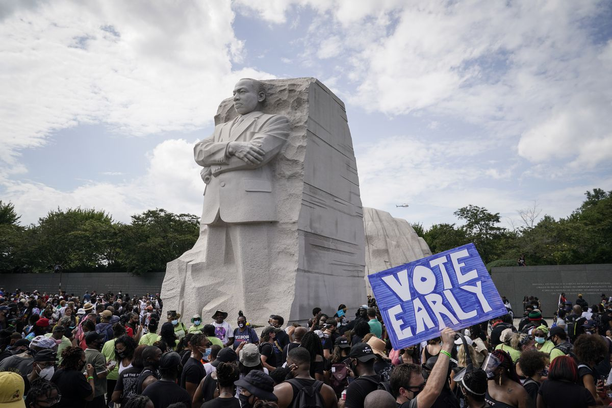 "One demonstrator in the crowd in front of the MLK Memorial holds a sign urging people to ""Vote early."""