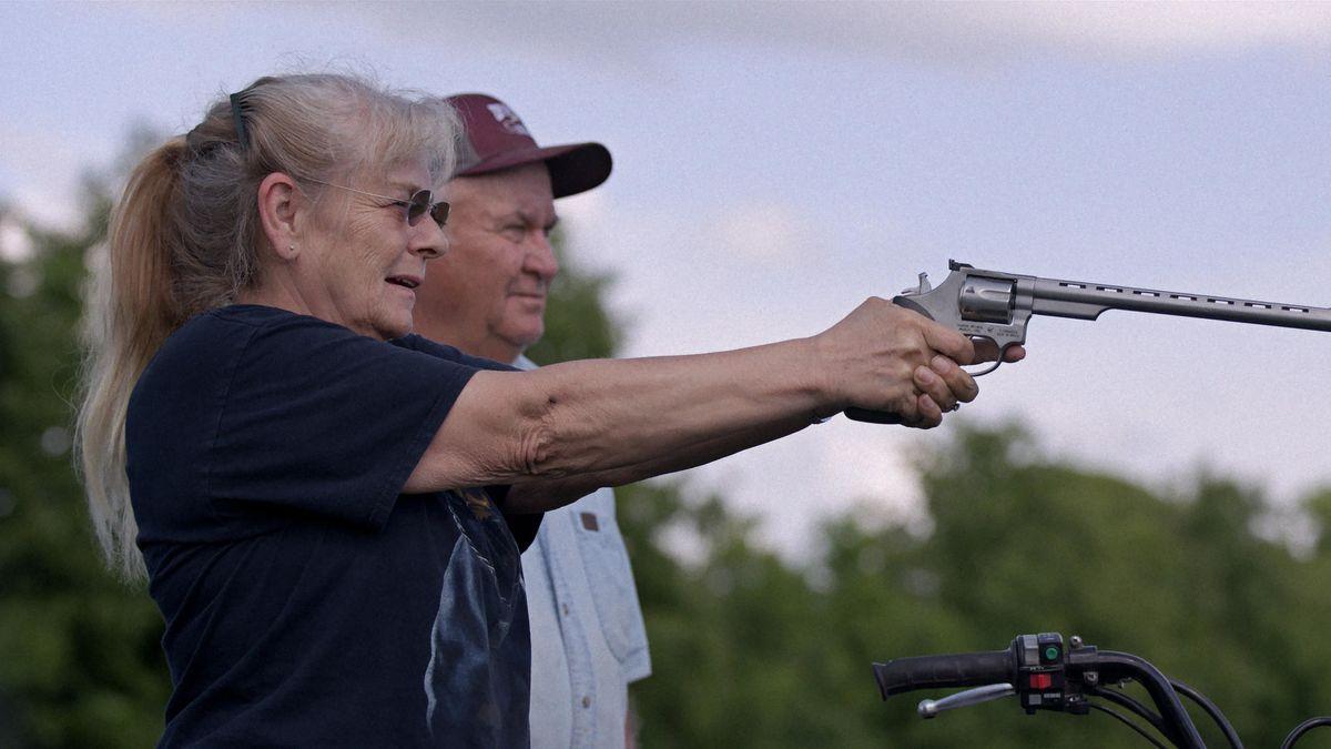 A woman with long grey hair points a handgun.