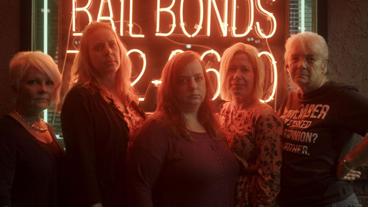 A group of women stands in front of a neon-lit screen.