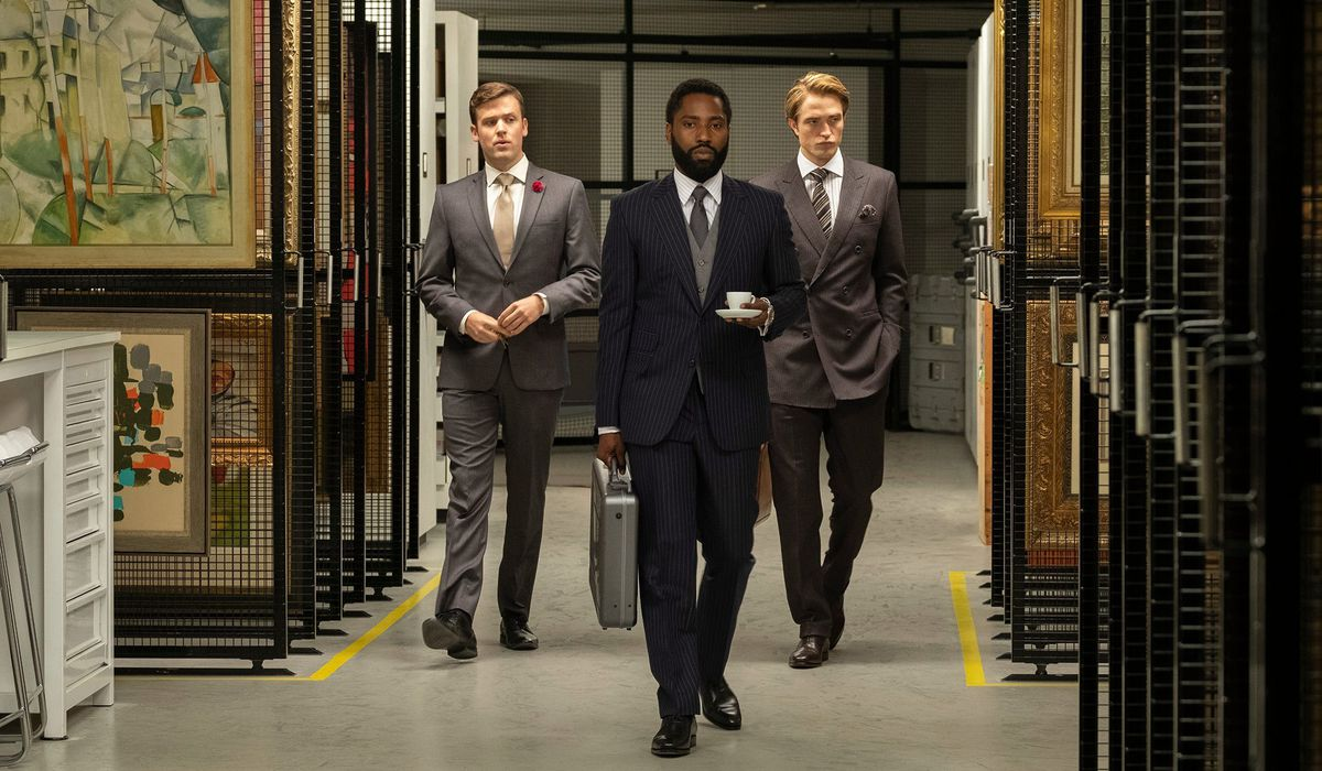 Three men in suits walk through a room containing art.