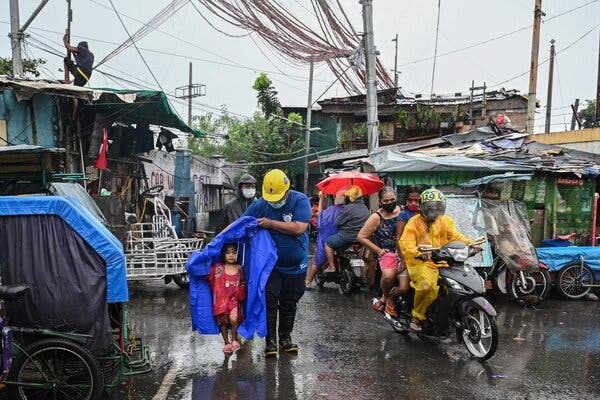 A rescue worker escorted a child during an evacuation of people living along coastal areas in Manila on Sunday.